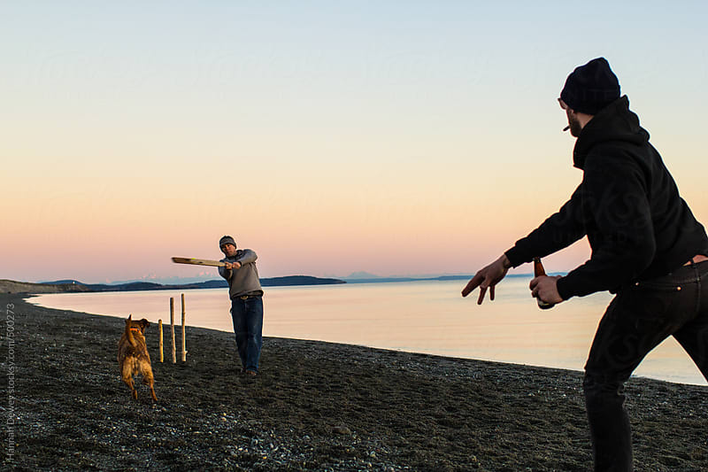 Two men and a dog play driftwood baseball on the beach by Hannah Dewey for Stocksy United