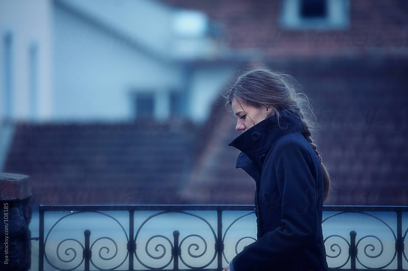 Young woman in foggy autumn town by Ilya for Stocksy United