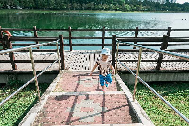 Little boy at lake park by Alita Ong for Stocksy United