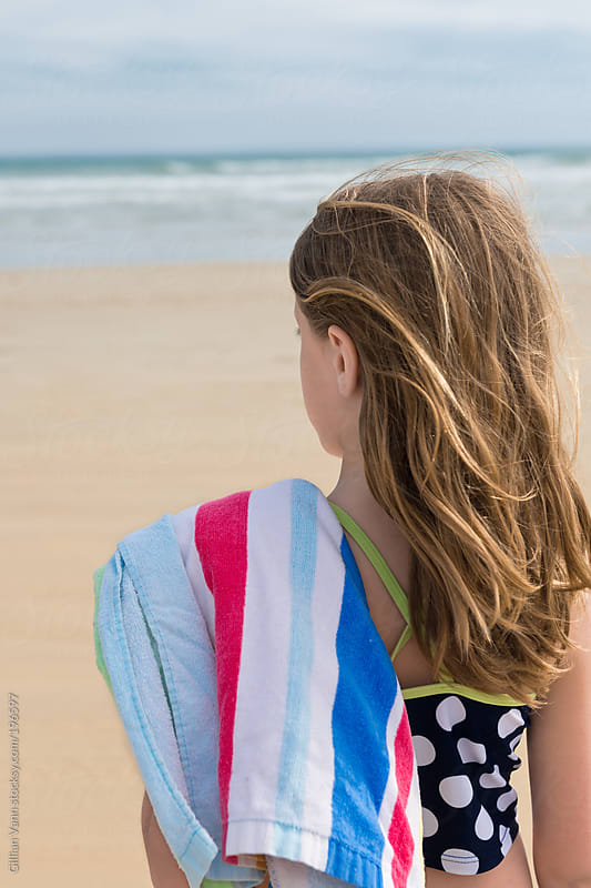 girl at beach with striped towell by Gillian Vann for Stocksy United