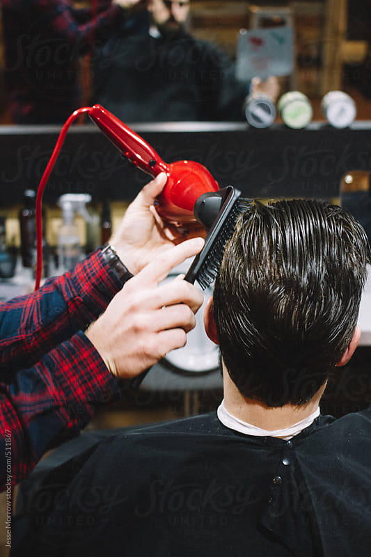 Barber blows hair dry during haircut by Jesse Morrow for Stocksy United