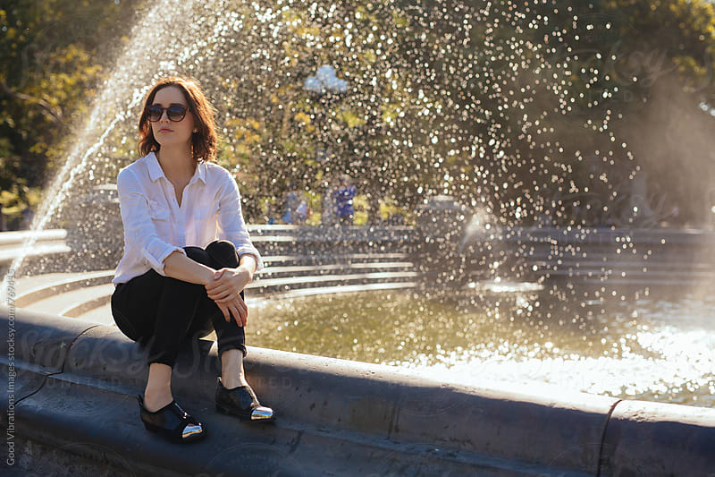 Smiling woman at the park sitting next to a fountain by Good Vibrations Images for Stocksy United