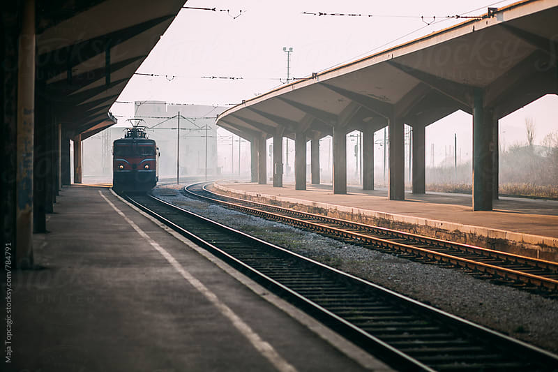 Retro train station with train coming in by Maja Topcagic for Stocksy United