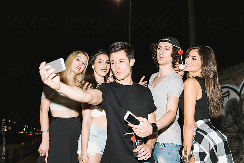 Group of friends taking a selfie in the nightlife by GIC for Stocksy United