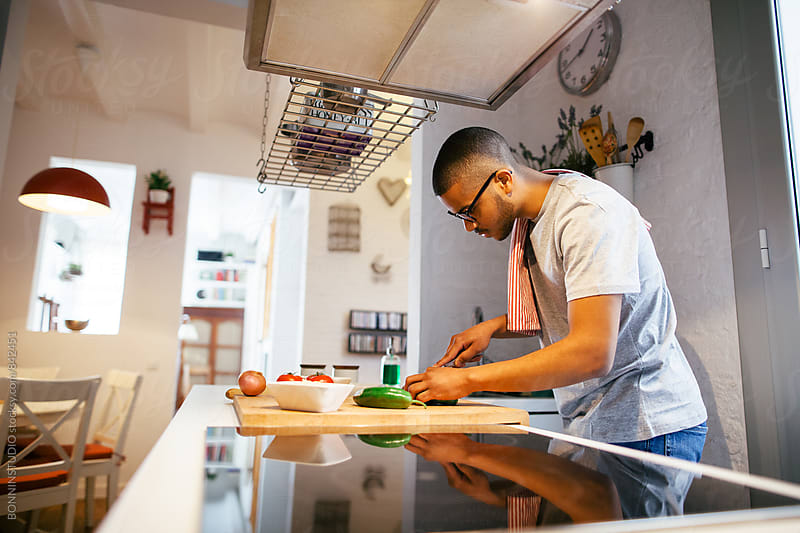 Side view of a man cutting vegetables to make a handmade pizza in the kitchen. by BONNINSTUDIO for Stocksy United