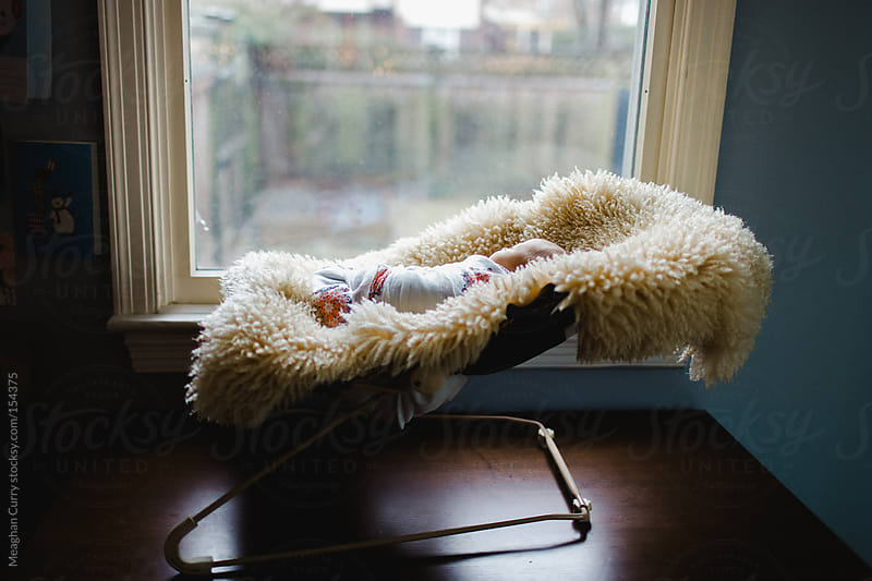 newborn in a bouncy chair looking out the window by Meaghan Curry for Stocksy United