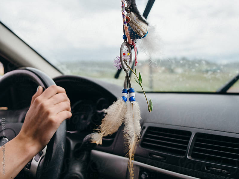 Woman's hand on steering wheel. Dreamcatcher hanging. by Jeremy Pawlowski for Stocksy United