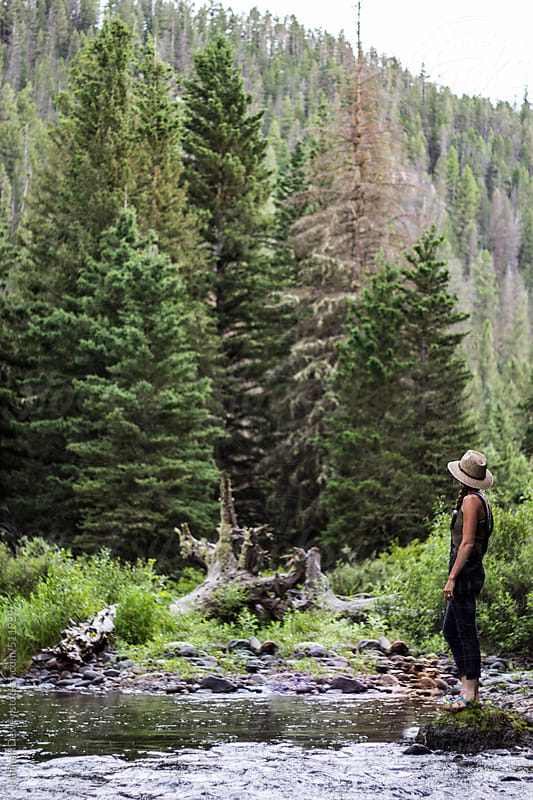 Woman stands on a rock in the river looking out into the evergreen forest by Hannah Dewey for Stocksy United