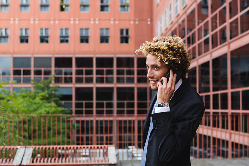 Smiling elegant man calling with his mobile phone by michela ravasio for Stocksy United