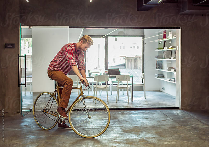 Man Riding a Bicycle Indoors by Lumina for Stocksy United