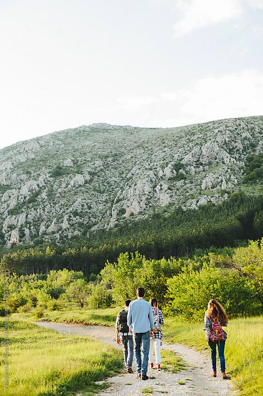 Group of friends walking in nature by Aleksandar Novoselski for Stocksy United