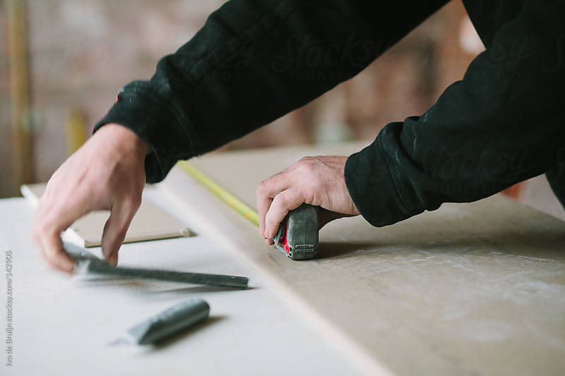 Arms of man who is measuring plasterboard on a workbench by Ivo de Bruijn for Stocksy United