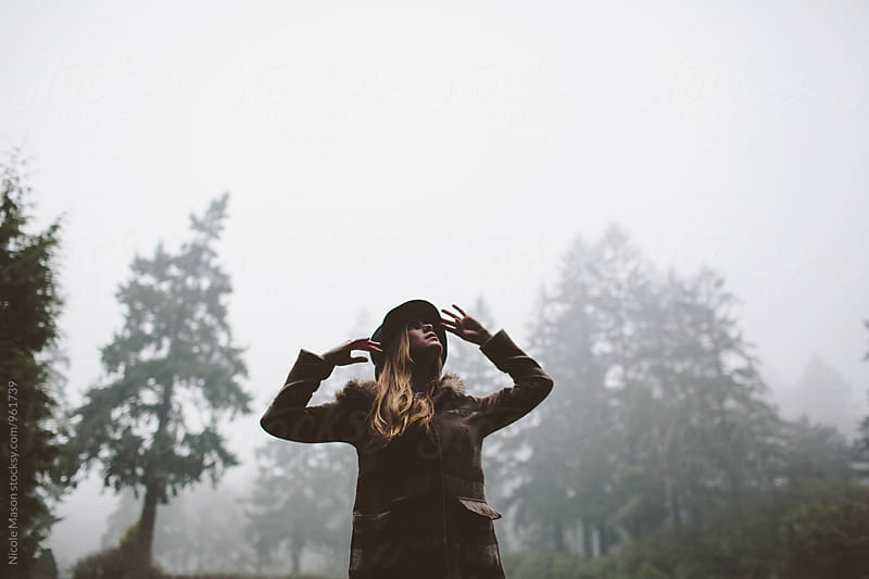 young woman standing in foggy park with tall trees by Nicole Mason for Stocksy United