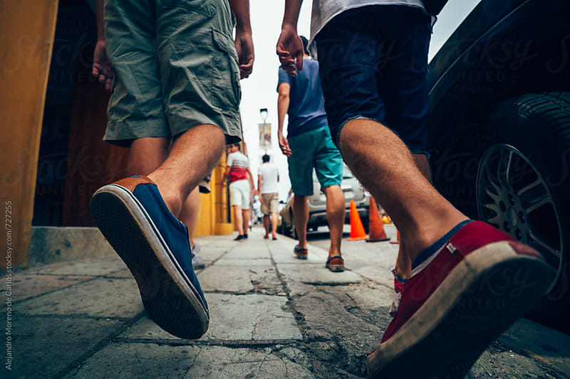 Low angle shot of the feet of some men friends walking down a street by Alejandro Moreno de Carlos for Stocksy United