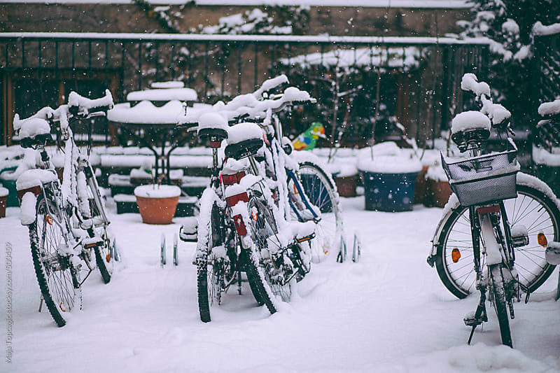 Parked bikes in a building garden full of snow by Maja Topcagic for Stocksy United