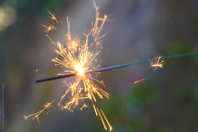 Sparks flying off a sparkler - celebration by Carolyn Lagattuta for Stocksy United