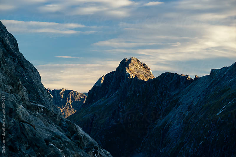 evening light catches the top of a mountain peak by Christian McLeod Photography for Stocksy United