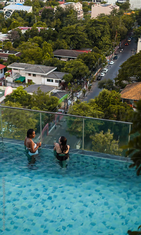 Girlfrends relaxing in rooftop swimming pool with city/city streets in background. by Marko Milanovic for Stocksy United