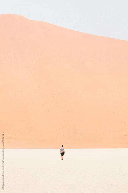 Far away wiew of a young man walking in the middle of the desert with a big sand dune in front by Alejandro Moreno de Carlos for Stocksy United