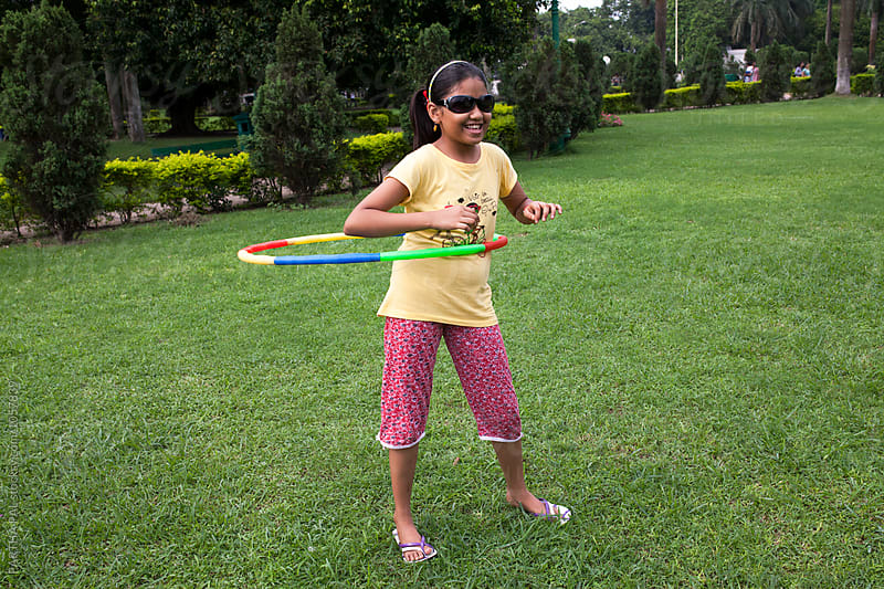 Teenage girl playing with Hula Hoop by PARTHA PAL for Stocksy United