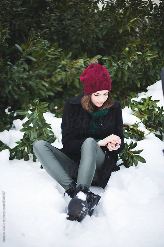 Winter portrait of a beautiful brunette sitting in the snow by Natasa Kukic for Stocksy United