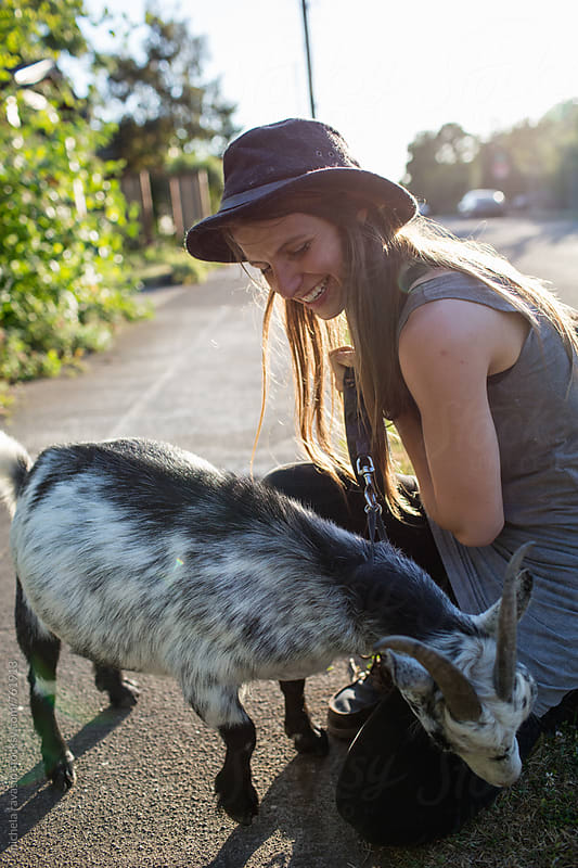 Girl playing with her goat by michela ravasio for Stocksy United