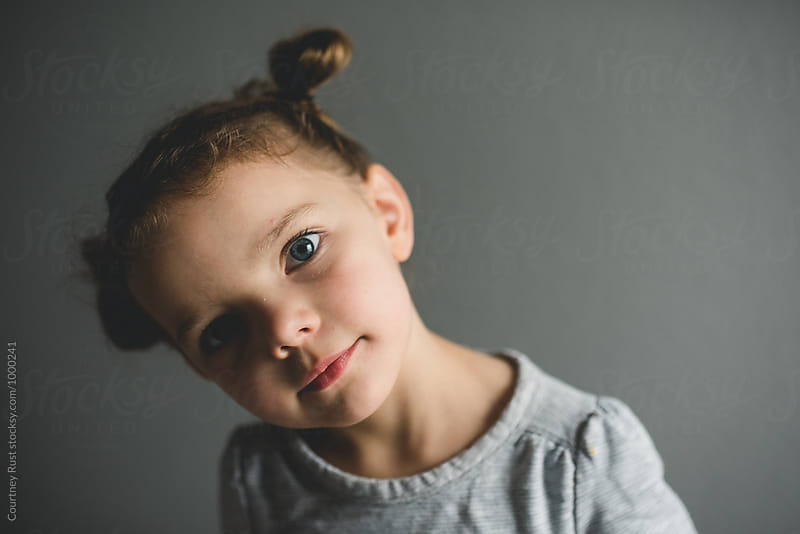 Funny look from child in pigtail buns by Courtney Rust for Stocksy United