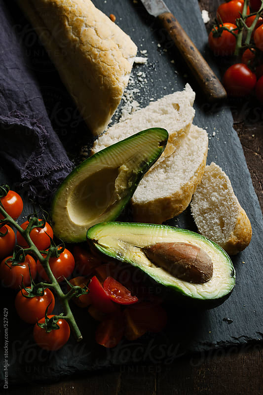 Making avocado and tomato crostini. by Darren Muir for Stocksy United