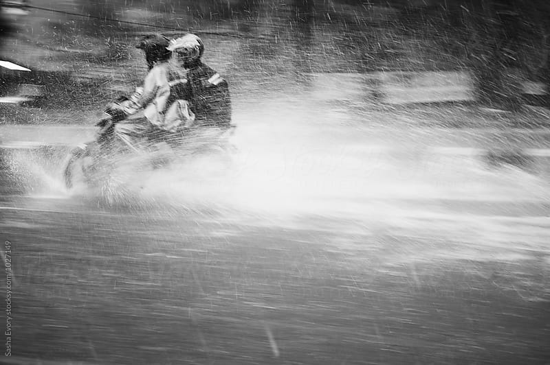 Two in the motorbike driving through the heavy rain by Sasha Evory for Stocksy United