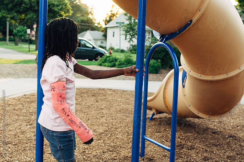 Black girl with pink cast hanging out at a playground at sunset by Gabriel (Gabi) Bucataru for Stocksy United
