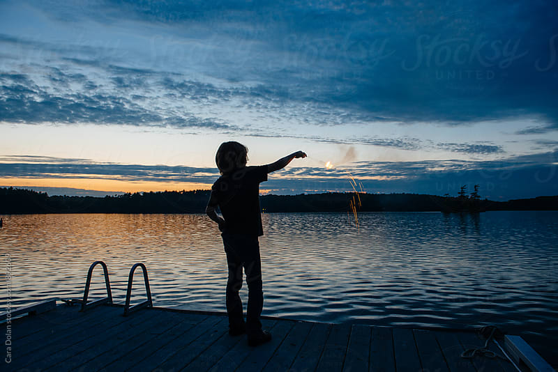 Boy at the lake plays with sparklers by Cara Slifka for Stocksy United
