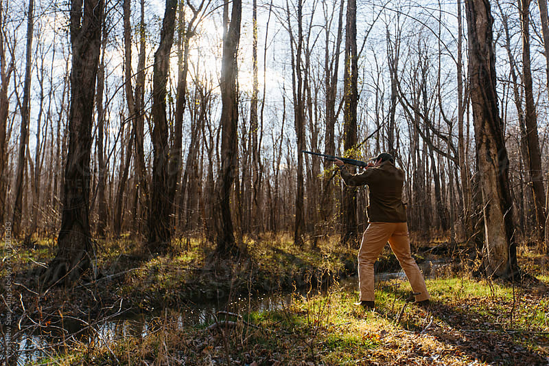 Man pointing and aiming gun in woods while hunting outdoors by Matthew Spaulding for Stocksy United