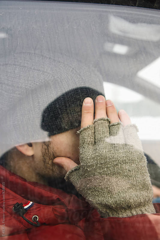 Close-up of man hiding his face with hand by Danil Nevsky for Stocksy United
