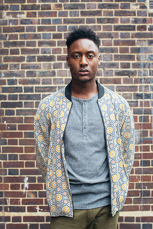 London Street Style - Outdoor Portrait of Young Casual Black Man Standing in Front of Exposed Brick Wall by Julien L. Balmer for Stocksy United