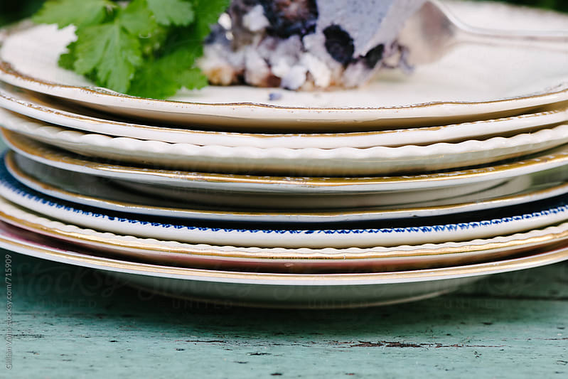 stacked mismatched vintage plates by Gillian Vann for Stocksy United