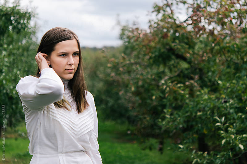 Teen Girl Standing in Apple Orchard by Deirdre Malfatto for Stocksy United