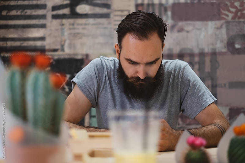 Serious Bearded Man Sitting in a Cafe by Katarina Radovic for Stocksy United