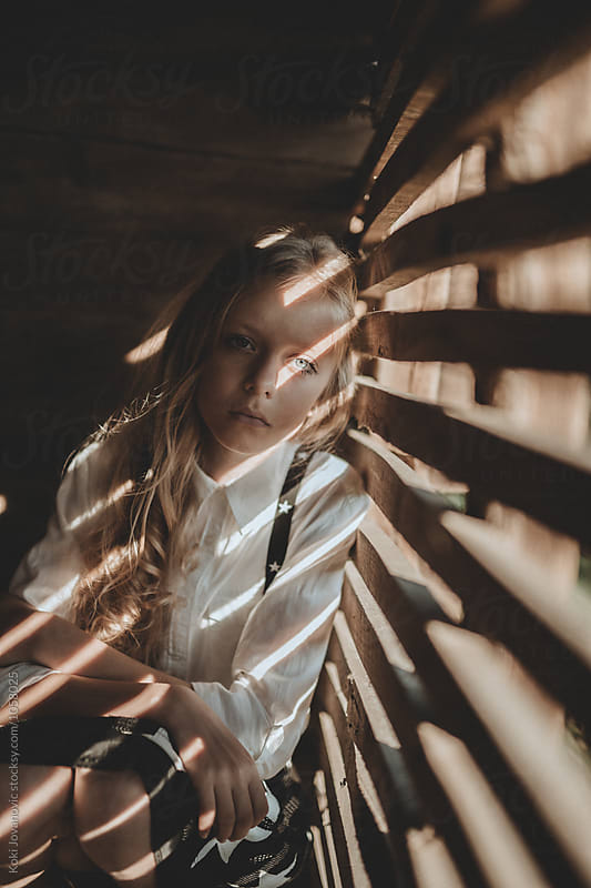 girl looking thru barn door by Koki Jovanovic for Stocksy United