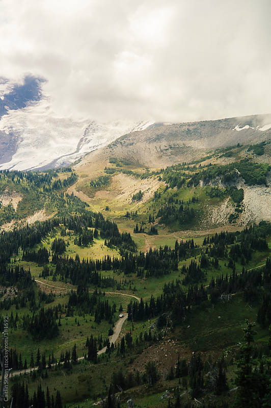 Lonely car and road under Mount Rainier by Caitlin Strom for Stocksy United