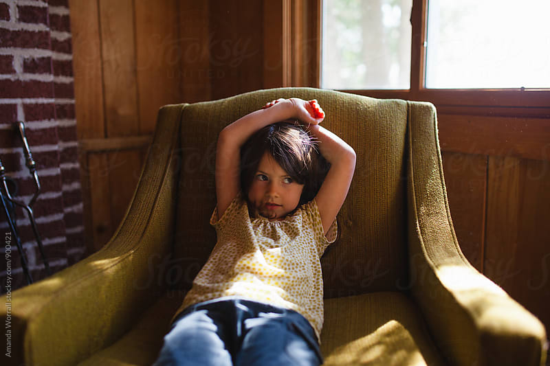 Little girl sitting back in vintage chair with bored expression by Amanda Worrall for Stocksy United