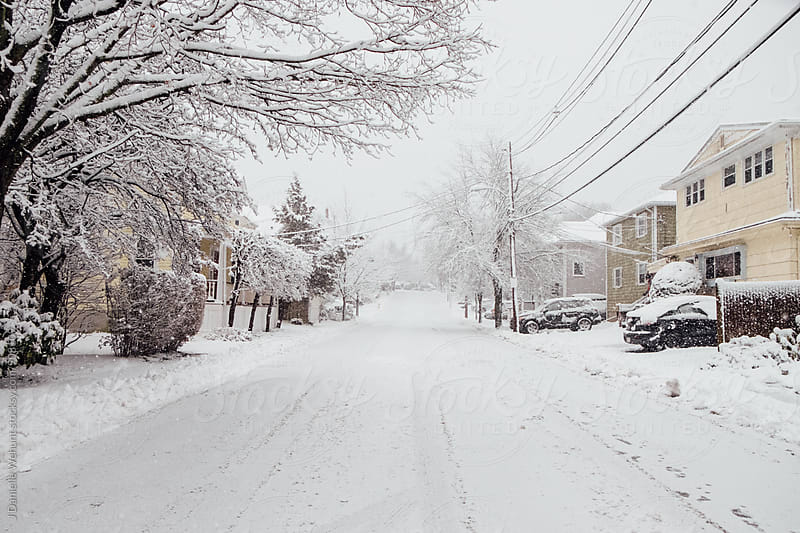 A street view of a snow covered road in a residential new england neighborhood by J Danielle Wehunt for Stocksy United