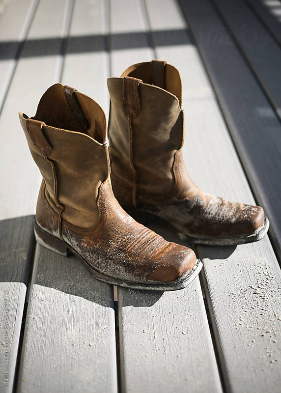Empty sand covered leather cowboy boots on wood deck in sunlight by Matthew Spaulding for Stocksy United