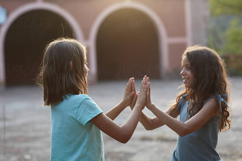 Two young girls playing and having fun at sunset by Miquel Llonch for Stocksy United