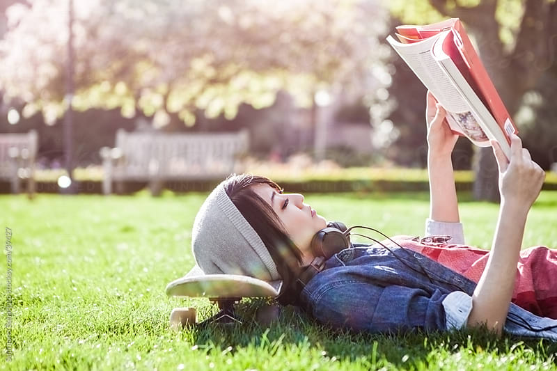 Asian college student studying while lying down on the grass by Suprijono Suharjoto for Stocksy United