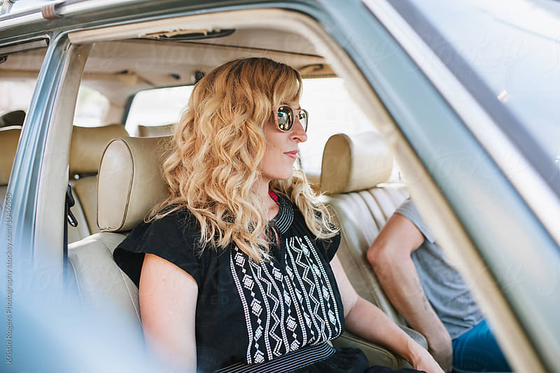 woman sitting in old station wagon with sunglasses on by Kristin Rogers Photography for Stocksy United