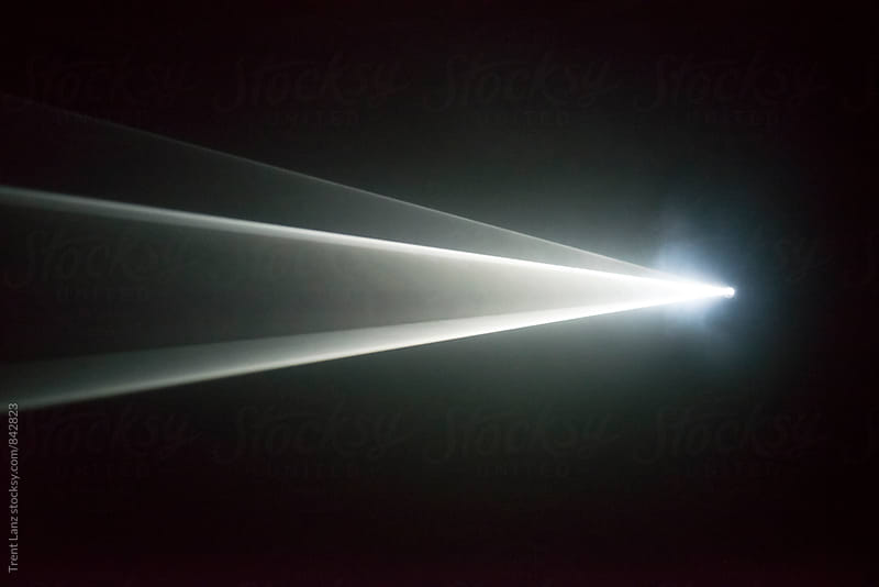 Illuminated beam of light from a projector by Trent Lanz for Stocksy United