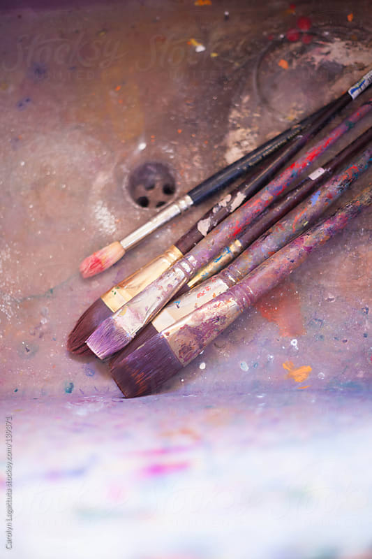 An artist's brushes in the sink - splattered with paint by Carolyn Lagattuta for Stocksy United