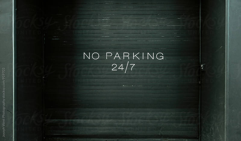 A no parking sign on a roll down door by Joseph West Photography for Stocksy United