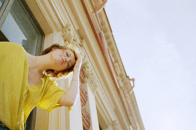 Young woman fixing her hair on the balcony by Lyuba Burakova for Stocksy United