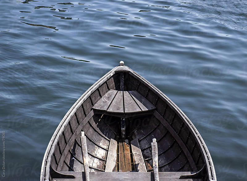 Empty wooden rowboat floating in calm waters by Cara Dolan for Stocksy United